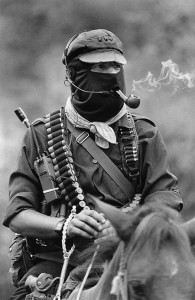 Subcomandante Marcos, the spokesman of the Ejército Zapatista de Liberación Nacional, smoking a pipe atop a horse in Chiapas, Mexico
