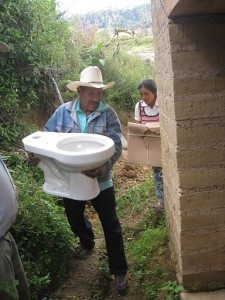 Mixteco family from Mini Numa, Guerrero carrying their new toilet to an adobe bathroom for installation; photo by Daniel Moss