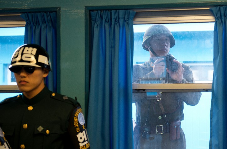 A North Korean Soldier takes photos through the window while U.S. Army Gen Martin E. Dempsey, chairman of the Joint Chiefs of Staff, is briefed at the demilitarized zone in South Korea, Nov. 11, 2012. (DOD photo by D. Myles Cullen/Released)