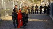 Two US Army (USA) Military Police (MP) escort a detainee, dressed in his new orange jumpsuit to a cell at Camp X-Ray, Guantanamo Bay Navy Base, Cuba. Camp X-Ray is the holding facility for detainees held at the US Navy (USN) Base during Operation ENDURING FREEDOM.